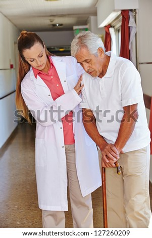 Nurse helping senior man with cane in a nursing home