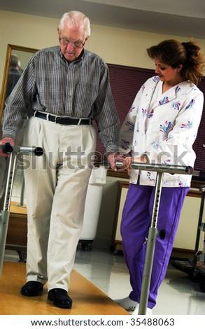 nurse helping senior man with physical rehabilitation - stock photo