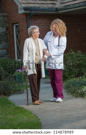Nurse Helping Senior Walking with Cane Outdoor in Early Morning Outside House - stock photo