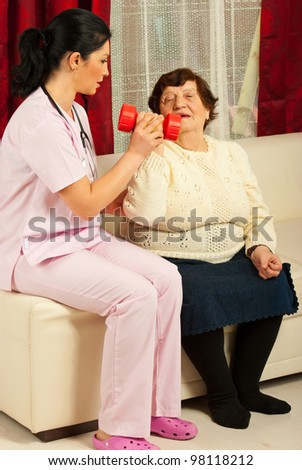 Nurse helping senior woman and explaining how to make therapy exercises in her home