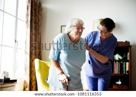 Nurse helping senior woman to stand