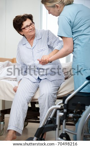 Nurse helps a patient to get up in hospital