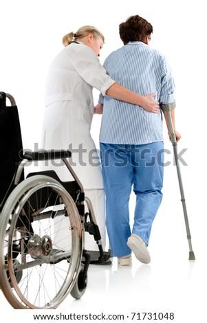 nurse helps a senior woman on crutches - stock photo