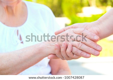 Nurse helps elderly woman in nursing home yard. Young girl helping old senior lady to get up, holding wrinkled hands, outdoors of health care hospital facility on the sunny day. Close up, background. #1007428087