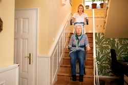 Nurse helps senior woman to climb to the stairs at nursing home