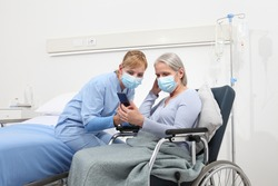 nurse helps with cell phone to contact the elderly lady's family in the wheelchair, wearing surgical protective medical masks in hospital room, concept of isolation from corona virus covid 19