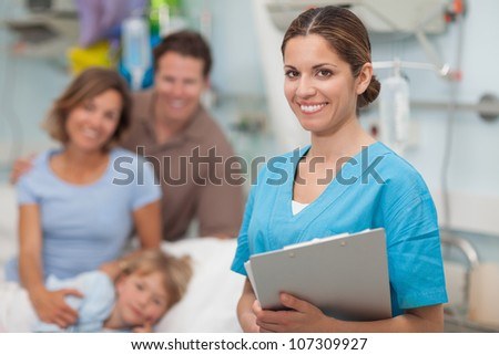 Nurse holding a clipboard next to a family in hospital ward