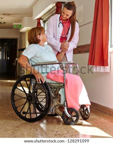 Nurse holding hand of female senior patient in wheelchair