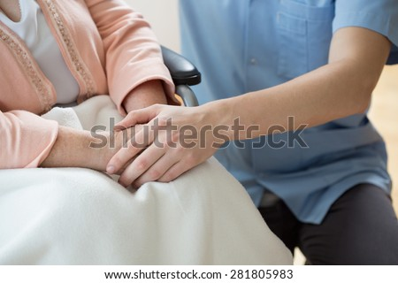 Nurse holding hands of a woman on a wheelchair
