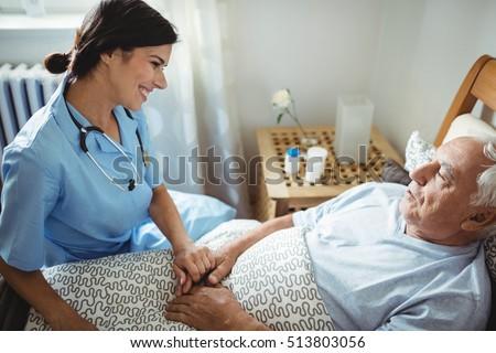 Nurse holding hands of senior man in bedroom