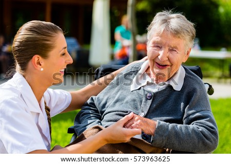 Nurse holding hands with senior woman sitting in wheelchair in garden of retirement home #573963625