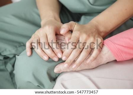 Nurse holding the hand of an elderly woman - closeup detail image.