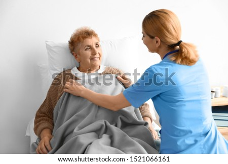 Nurse in uniform assisting elderly woman indoors