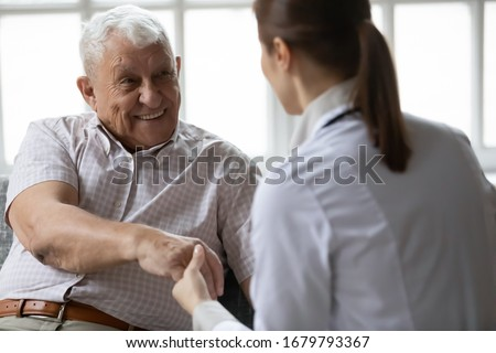 Nurse in uniform talking during day visit to old patient. Caring caregiver hold hand of 80s man people having pleasant conversation, satisfied grandfather receiving support and care from carer concept