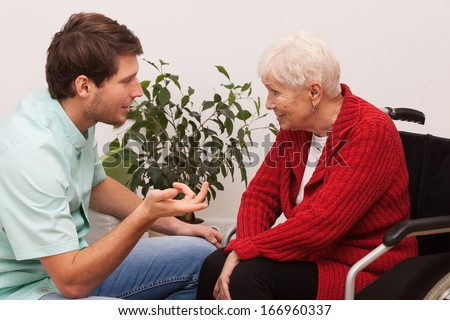 Nurse keeping company to disabled elderly lonely person