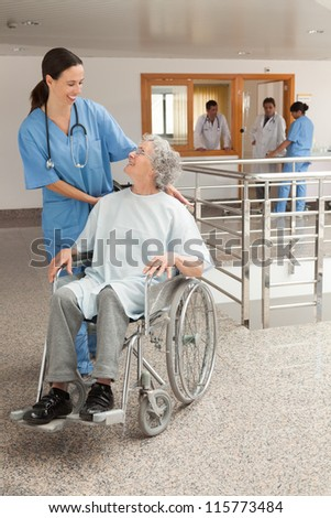 Nurse laughing with old women sitting in wheelchair in hospital corridor