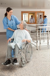 Nurse laughing with old women sitting in wheelchair in hospital corridor, Healthcare workers in the Coronavirus Covid19 pandemic