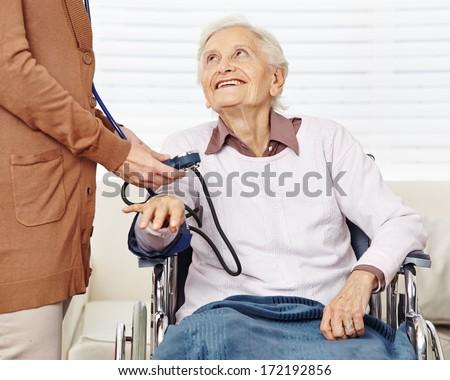 Nurse measuring blood pressure for senior woman in wheelchair in a nursing home