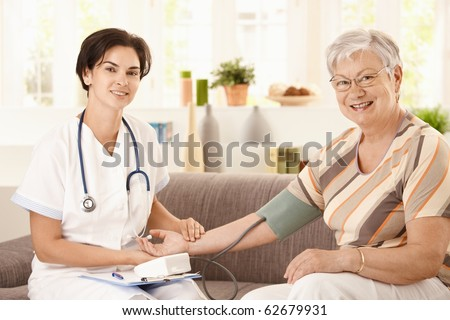 Nurse measuring blood pressure of senior woman at home. Looking at camera, smiling.?