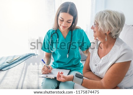 Nurse measuring blood pressure of senior woman at home. Smiling to each other. Young nurse measuring blood pressure of elderly woman at home. Doctor checking elderly woman's blood pressure