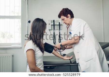 Nurse measuring her patient\'s heart pressure. Interacting and taking care of patient. Taking care of your health. Disease prevention.