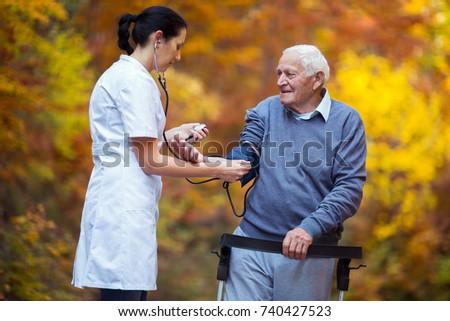 Nurse measuring old patient's blood pressure outdoor #740427523