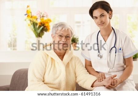 Nurse measuring pulse rate of senior woman at home. Looking at camera, smiling.?