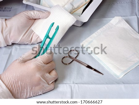 Nurse prepares wound dressing tray materials for use on a patient.