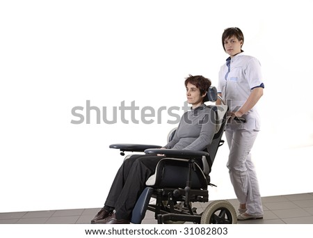 nurse pushing a disabled woman in a wheelchair