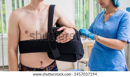 Nurse putting a sling on patients arm that is broken. Injury. Broken arm, shoulder. Arm fix brace