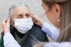 Nurse putting on surgical mask on elderly ill woman - coronavirus protective protocol