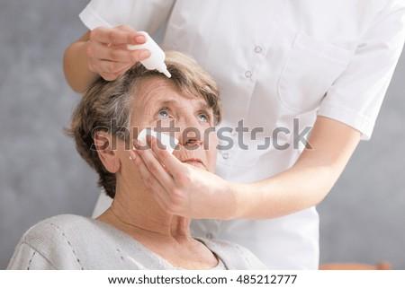Nurse putting the eye drops to senior woman's eyes