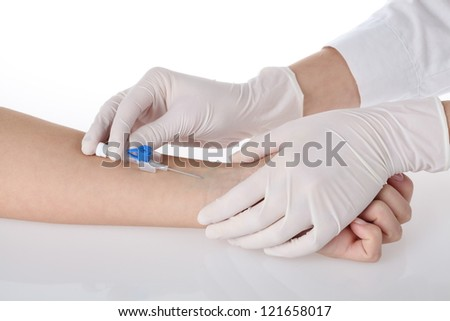 Nurse's hands putting intravenous cannula in patient's hand
