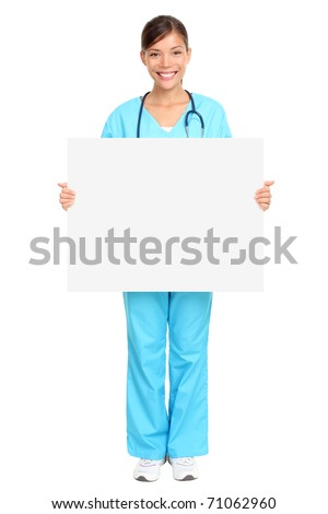 Nurse showing medical sign billboard standing in full length. Young smiling woman nurse or doctor in scrubs showing empty blank sign board with copy space. Asian model isolated on white background.