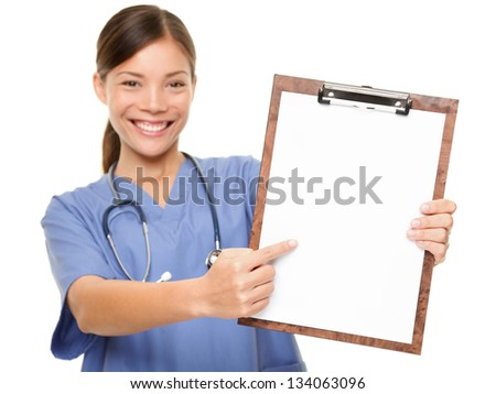 Nurse showing medical sign clipboard copy space. Female medical doctor or nurse pointing at blank empty copyspace. Young mixed race Asian Caucasian woman model in blue scrubs isolated on white.