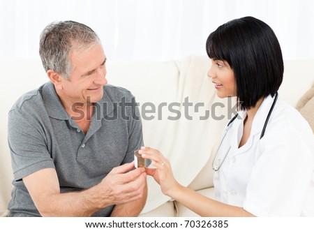 Nurse showing pills to her mature  patient