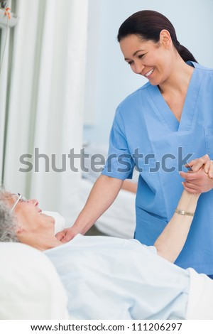 Nurse smiling to a patient while holding her hand in hospital ward