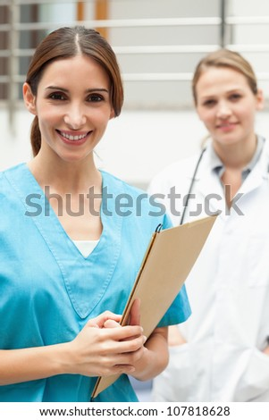 Nurse standing in a hospital reception with a doctor while smiling
