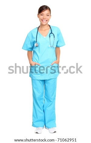 Nurse standing isolated. Young multiracial nurse or medical doctor standing isolated in full length wearing blue scrubs. - stock photo