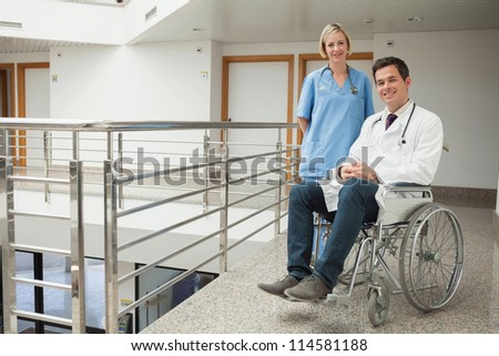 Nurse standing with doctor sitting in wheelchair in hospital corridor