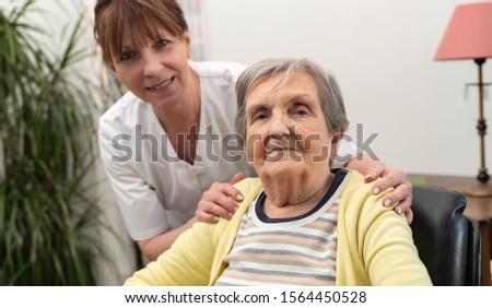 Nurse supporting elderly woman in nursing home