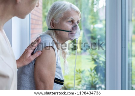 Nurse supporting sick senior woman with oxygen mask in the hospital #1198434736