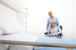 nurse take care elderly woman isolated on wheelchair near bed in hospital room, concept of loneliness and old age diseases