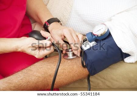 Nurse taking a patient's blood pressure using a sphygmomanometer.  Closeup view.