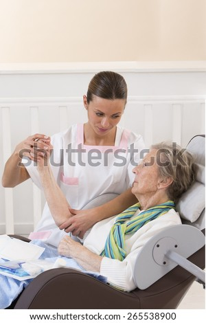 Nurse taking care of senior woman in retirement home bandaging her arm