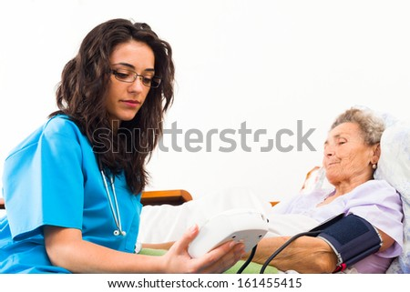 Nurse using digital blood pressure for senior patient