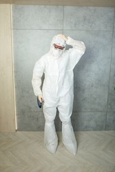 nurse wearing anticoronavirus Personal Protective Equipment, face shield, gloves and respirator stands with phonendoscope and keeps her head