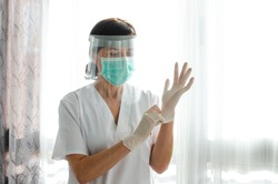 Nurse with a face shield putting on latex gloves
