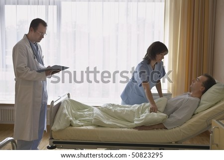 Nurse with doctor adjusting patient in bed in hospital