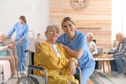 Nurse with elderly woman in wheelchair at retirement home. Assisting senior people